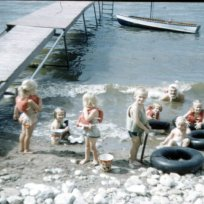 Dad (Uncle Tom Conard) swimming with what is presumed to be underwear on his head (we really have no idea) and assorted cousins in life jackets and black inner tubes waiting to go swimming.